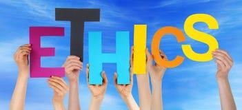 Leute-Hände, die bunte Wort-Ethik-blauen Himmel halten Lizenzfreie Stockfotografie