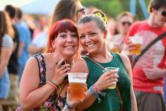 Leute haben trinkendes Bier des Spaßes und aufpassende Konzerte an FLUNKEREI Festival Stockfotografie
