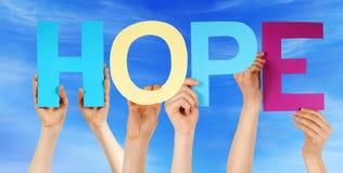 Leute halten bunte gerade Wort-Hoffnungs-blauen Himmel Stockbilder