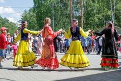 Leute halten die Hände und tanzen in einen Kreis Der Jahresnationalfeiertag der Tataren und der Bashkirs Sabantuy im Stadtpark lizenzfreies stockfoto