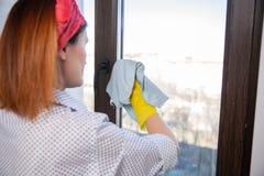 Leute-, Hausarbeit- und Haushaltungskonzept - Frau in den Handschuhen, die zu Hause Fenster mit Lappen säubern lizenzfreies stockbild