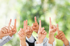 Leute heben ihre Hände oben über grünem Hintergrund an Lizenzfreies Stockbild