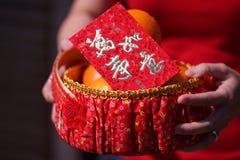 Leute hielten den orange Korb mit der Segnung des roten Umschlags für Geschenke des Chinesischen Neujahrsfests Stockfoto