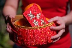 Leute hielten den orange Korb mit der Segnung des roten Umschlags für Geschenke des Chinesischen Neujahrsfests Lizenzfreie Stockfotos