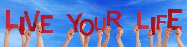 Leute-Hände halten rotes Wort Live Your Life Blue Sky Lizenzfreie Stockbilder