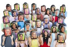Leute-Holding-Geräte mit ihrem Gesicht auf ihm Stockfoto