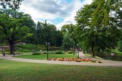 Leute im allgemeinen Park des Sommers mit Blumenbeet in Riga, Lettland, am 25. Juli 2018 lizenzfreie stockbilder
