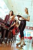 Leute im amerikanischen Restaurant oder Restaurant mit Kellnerin Lizenzfreie Stockbilder