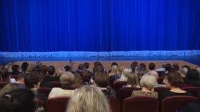 Leute im Auditorium des Theaters vor der Leistung oder in der Unterbrechung Blauer Vorhang auf Stadium stock video footage