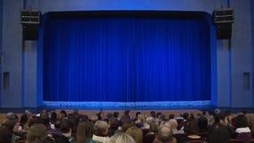Leute im Auditorium des Theaters vor der Leistung oder in der Unterbrechung Blauer Vorhang auf Stadium stock video