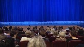 Leute im Auditorium des Theaters vor der Leistung oder in der Unterbrechung Blauer Vorhang auf Stadium Schießen von hinten stock footage