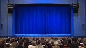 Leute im Auditorium des Theaters vor der Leistung oder in der Unterbrechung Blauer Vorhang auf Stadium Schießen von hinten stock video