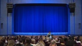 Leute im Auditorium des Theaters vor der Leistung oder in der Unterbrechung Blauer Vorhang auf Stadium Schießen von hinten stock video footage
