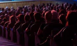 Leute im Auditorium, welches das Stadium betrachtet Schießen von der Rückseite Lizenzfreie Stockfotos