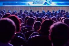 Leute im Auditorium, welches das Stadium betrachtet Schießen von der Rückseite Stockfotos