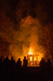 Leute im Hintergrund eines brennenden Hauses Stockfotografie