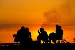 Leute im kampierenden Sitzen nahe Lagerfeuer gegen Sonnenuntergang Lizenzfreies Stockfoto
