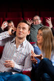 Leute im Kinotheater mit Handy Stockbild