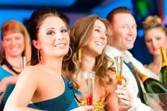 Leute im Klumpen oder in trinkendem Champagner des Stabes Lizenzfreie Stockbilder