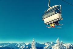 Leute im Sessellift am Skiort über schneebedeckten Bäumen und Berg Lizenzfreies Stockbild
