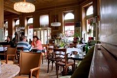 Leute innerhalb des alten Cafés mit historischem Innenraum Lizenzfreie Stockfotografie