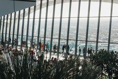 Leute innerhalb des Himmels arbeiten, London, die Stadtskyline im garten, die durch das Glas gesehen werden Stockfoto