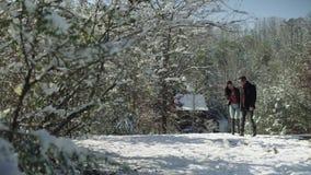 Leute-, Jahreszeit-, Liebes- und Freizeitkonzept - gl?ckliches Paar, das ?ber Winterhintergrund geht stock footage