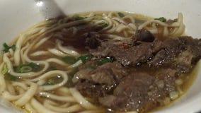 Leute 4K, die Stöcke für verwenden, traditionelle Rindfleischnudeln zu essen im asiatischen Restaurant stock video