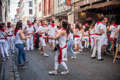 Leute kleideten beim dem weißen und roten Trinken und Tanzen in die Straßen am Sommerfestival an (Partyde Bayonne) Lizenzfreie Stockbilder
