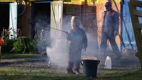 Leute kochen Lebensmittel auf dem Grill mit Rauche stock video
