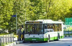 Leute kommen in den Bus an der Bushaltestelle stockbild