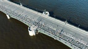 Leute lassen Marathon entlang Brücke über tiefem blauem Fluss laufen stock footage