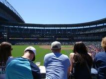 Leute lehnen sich auf Schiene und betrachten Baseballfeld Stockfotos