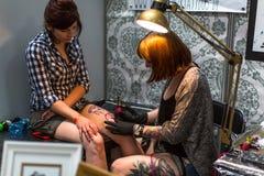 Leute machen Tätowierungen an der 10. internationalen Tätowierungs-Vereinbarung in der Kongress-AUSSTELLUNG Mitte Stockfotografie