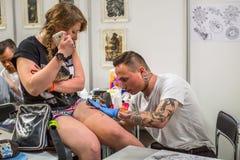 Leute machen Tätowierungen an der 10. internationalen Tätowierungs-Vereinbarung in der Kongress-AUSSTELLUNG Mitte Lizenzfreies Stockfoto