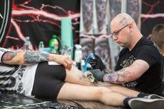 Leute machen Tätowierungen an der 10. internationalen Tätowierungs-Vereinbarung in der Kongress-AUSSTELLUNG Mitte Stockbilder