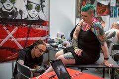 Leute machen Tätowierungen an der 10. internationalen Tätowierungs-Vereinbarung in der Kongress-AUSSTELLUNG Mitte Stockfoto