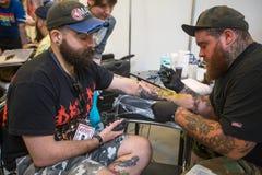 Leute machen Tätowierungen an der 10. internationalen Tätowierungs-Vereinbarung in der Kongress-AUSSTELLUNG Mitte Lizenzfreie Stockfotografie