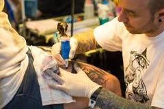 Leute machen Tätowierungen an der 10. internationalen Tätowierungs-Vereinbarung in der Kongress-AUSSTELLUNG Mitte Lizenzfreie Stockbilder