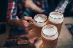 Leute-, Mann-, Freizeit-, Freundschafts- und Feierkonzept - glückliche männliche Freunde, die Bier trinken und Gläser an der Bar  Stockbilder
