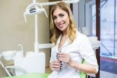 Leute-, Medizin-, Stomatologie- und Gesundheitswesenkonzept - glücklicher junger weiblicher Zahnarzt mit Werkzeugen über Hintergr stockbilder