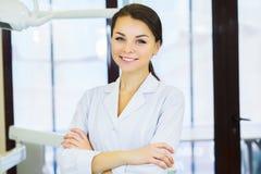 Leute-, Medizin-, Stomatologie- und Gesundheitswesenkonzept - glücklicher junger weiblicher Zahnarzt mit Werkzeugen über Hintergr lizenzfreie stockfotografie