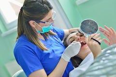 Leute-, Medizin-, Stomatologie- und Gesundheitswesenkonzept - glücklicher weiblicher Zahnarzt, der geduldige Mädchenzähne überprü stockfoto