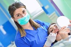 Leute-, Medizin-, Stomatologie- und Gesundheitswesenkonzept - glücklicher weiblicher Zahnarzt, der geduldige Mädchenzähne überprü stockfotos