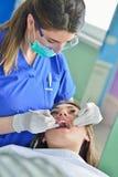 Leute-, Medizin-, Stomatologie- und Gesundheitswesenkonzept - glücklicher weiblicher Zahnarzt, der geduldige Mädchenzähne überprü lizenzfreies stockbild