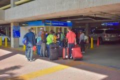 Leute mit dem Gepäck, das in Miete ein Auto wartend hereinkommt bei Orlando International Airport stockfotos