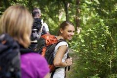 Leute mit dem Rucksack, der Trekking im Holz tut stockbild