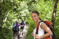 Leute mit dem Rucksack, der Trekking im Holz tut lizenzfreies stockbild
