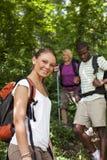 Leute mit dem Rucksack, der Trekking im Holz tut lizenzfreie stockfotos