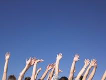 Leute mit den Armen angehoben Stockbild